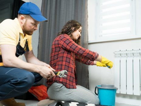 Serious attractive young lady in casual shirt and rubber gloves squeezing cloth while mopping floor from radiator water, repairman in cap sitting near her and waiting when he will start working
